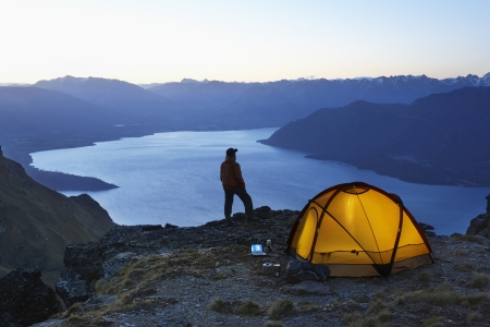 only mid adult men: Man looking at lake next to tent at dusk