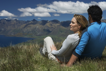 sit around: Couple cuddling looking over lake and hills