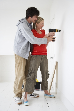 casual hooded top: Couple drilling inside their new home LANG_EVOIMAGES