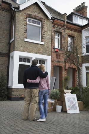 house series: Couple looking at house with possessions outside