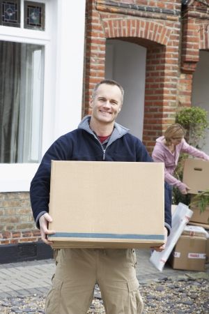 one person with others: Portrait of man holding box outside house