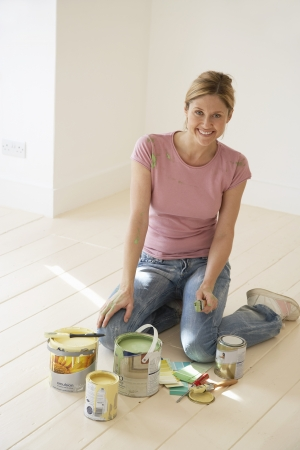 woman kneeling: Woman kneeling on floor with painting materials