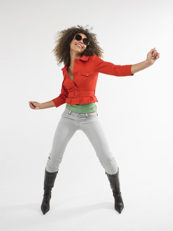legs wide open: Woman with curly hair wearing sunglasses dancing  in studio