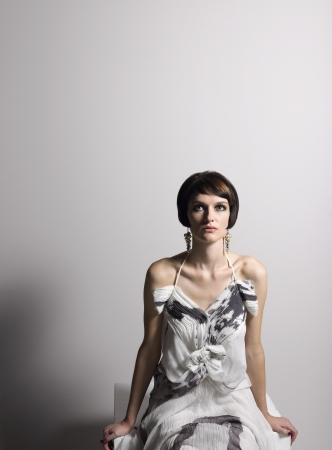 shouldered: Woman in dress sitting in studio