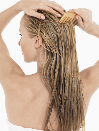 wet: Young Blond Woman Combing wet Hair back view