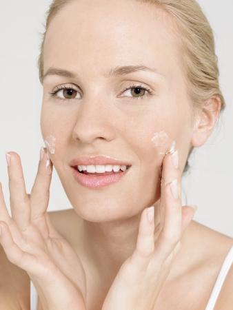 cremas faciales: Mujer joven que aplica la crema facial LANG_EVOIMAGES