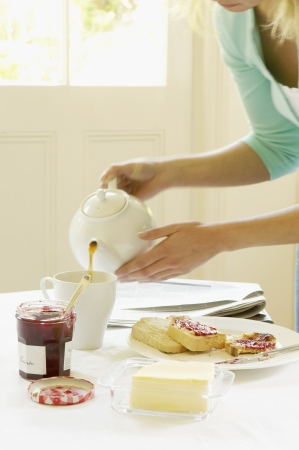 Woman Pouring Tea at Breakfast Stock Photo - 18884149
