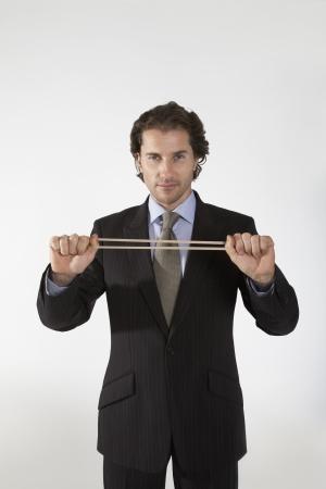 misbehavior: Businessman Stretching Rubber Band LANG_EVOIMAGES