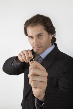 misbehaving: Businessman Aiming Rubber Band LANG_EVOIMAGES