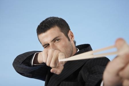 misbehaving: Businessman Stretching Rubber Band LANG_EVOIMAGES