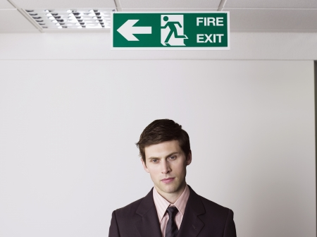 exit sign: Businessman Standing Under Exit Sign