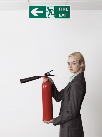 Businesswoman Holding Fire Extinguisher Under Exit Sign Stock Photo - 18884814
