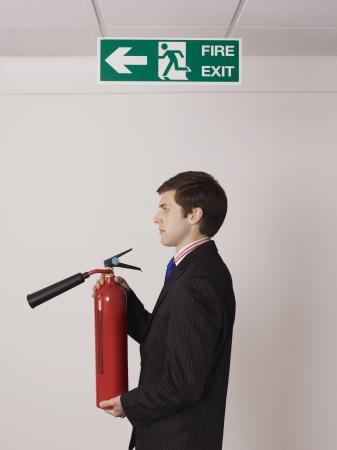 under fire: Empresario Sosteniendo Extintor Fuego bajo el signo de la salida