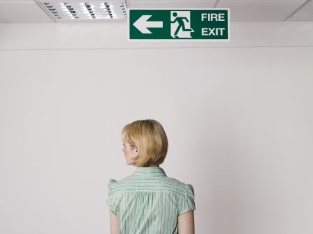 exit sign: Businesswoman Standing Under Exit Sign LANG_EVOIMAGES