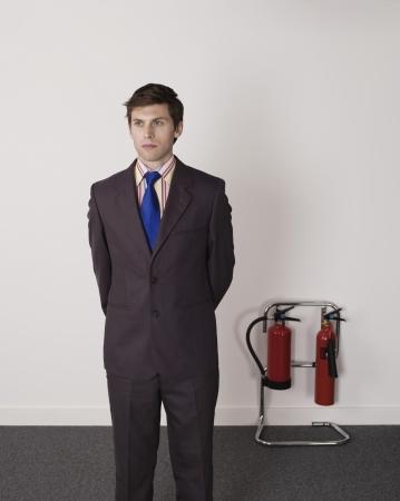 pensiveness: Businessman Standing Near Office Fire Extinguisher