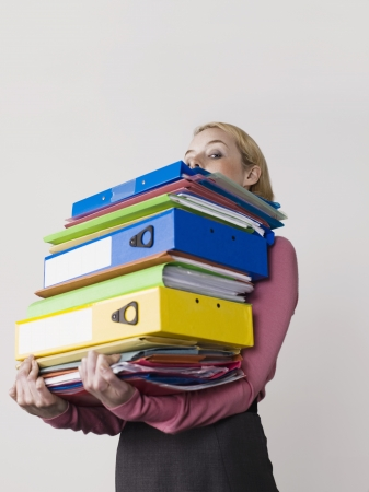 large group of items: Businesswoman Carrying Too Many Binders