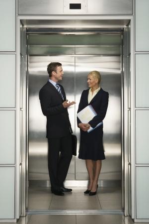 Businesspeople Talking in Elevator (elevator)