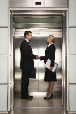 deal making: Businesspeople Shaking Hands in Elevator
