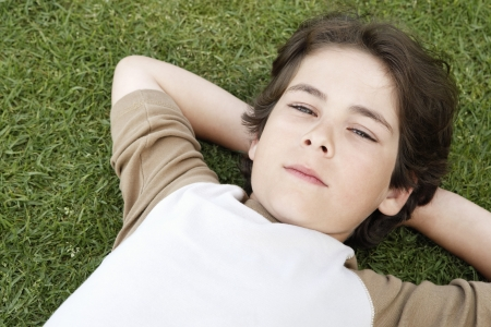 preadolescence: Little Boy Lying on the Grass LANG_EVOIMAGES