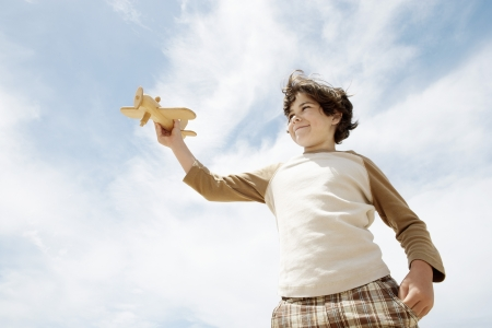 preadolescence: Little Boy with a Toy Airplane LANG_EVOIMAGES