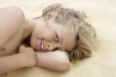tween boy: Little Boy Lying on the Sand