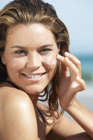basking: Young Woman Putting Sunscreen on Face