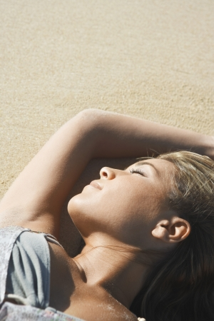 vacationer: Young Woman Sunbathing on Beach