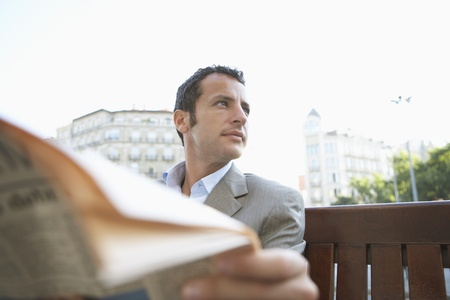labouring: Businessman Reading Newspaper Outdoors