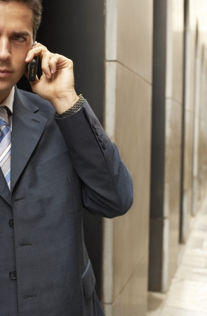 businessman waiting call: Businessman Using Cell Phone Outside Office Building
