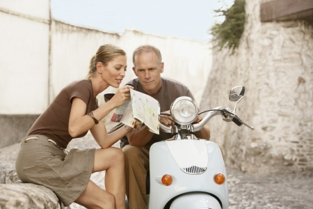 late 40s: Couple With Scooter Reading Map LANG_EVOIMAGES