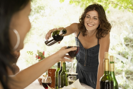 entertaining: Woman Pouring Wine at Dinner Party