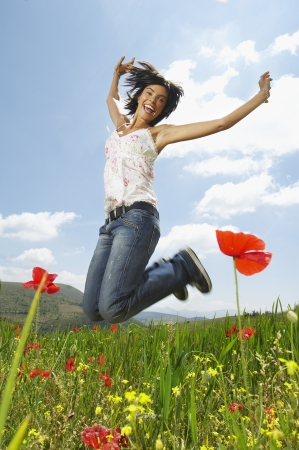 midair: Woman jumping for joy in mountain meadow, portrait