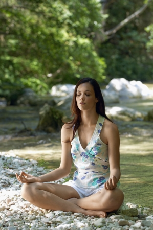 Young woman meditating by forest river, full length Stock Photo - 18886220