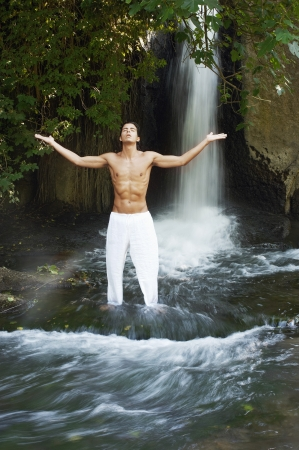 outstretched: Man standing in river by waterfall meditating, front view, full length LANG_EVOIMAGES