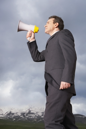 late 40s: Businessman Speaking Through a Megaphone LANG_EVOIMAGES