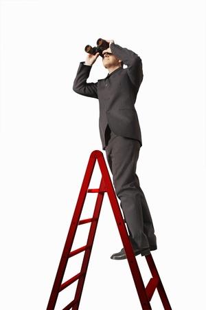 silhouettable: Uomo d'affari con il binocolo su Scala