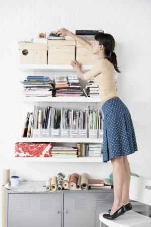 Woman Reaching for Shelf Stock Photo - 18885393