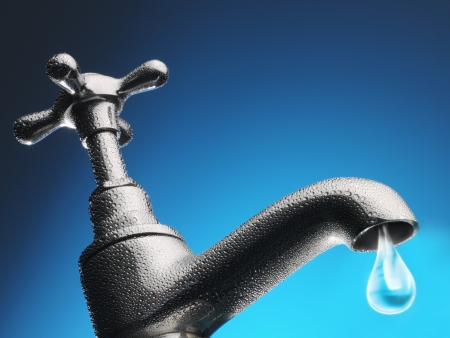 scarcity: Drop of water trickling from tap close-up (digital composite)