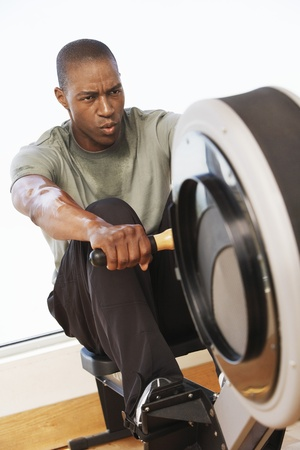 exerting: Man Using a Rowing Machine