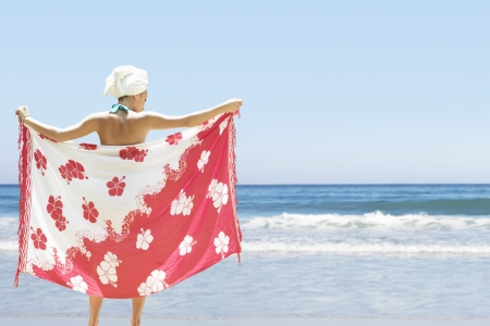partially nude: Woman holding sarong on beach back view LANG_EVOIMAGES