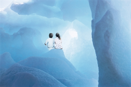 digital composite: Boy (3-4) and girl (5-6), wearing pyjamas, sitting in icy cave, back view (digital composite)