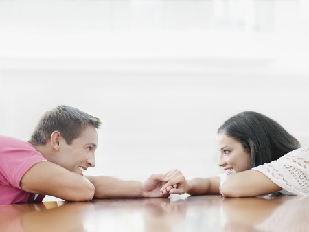 polished floor: Couple lying face to face on polished floor, holding hands, side view