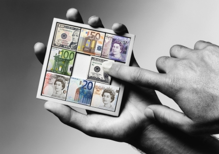 unknown age: Man holding sliding tile puzzle with tiles representing various currencies, close-up of hands, colour enhanced LANG_EVOIMAGES