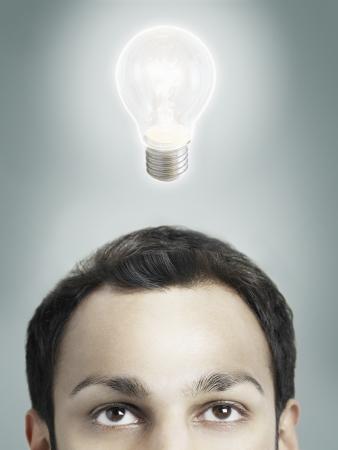 high section: Illuminated lightbulb over mans head high section studio shot