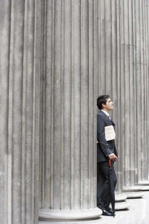 beforehand: Businessman Leaning on Pillar LANG_EVOIMAGES