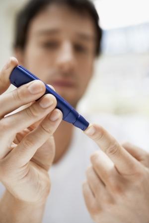 diabetes meter kit: Man using lancelet on finger in bathroom close up