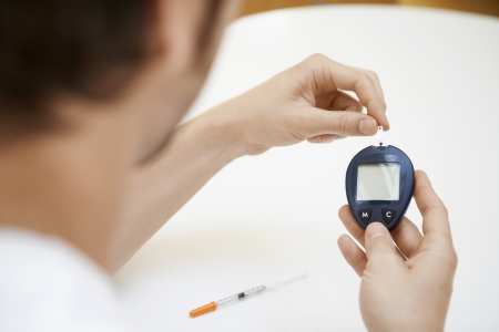 self testing: Man Using Blood Sugar Meter in bathroom