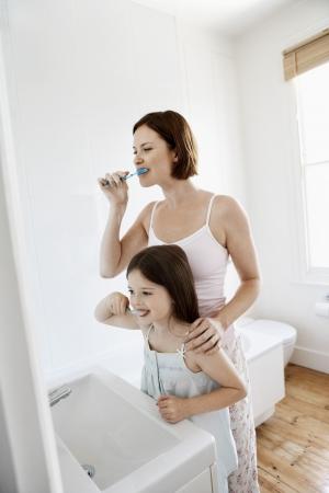 adult brushing teeth: Mother and Daughter Brushing Teeth in bathroom LANG_EVOIMAGES