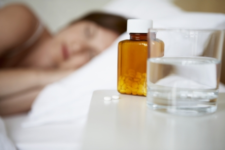 bedside: Sick woman in bed by pills on bedside table focus on foreground