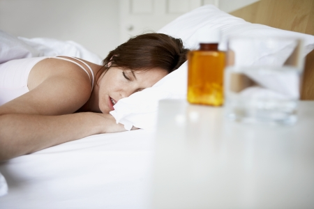 'bedside table': Sick woman in bed by pills on bedside table LANG_EVOIMAGES